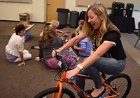 young woman rides child's bicycle as others build another one